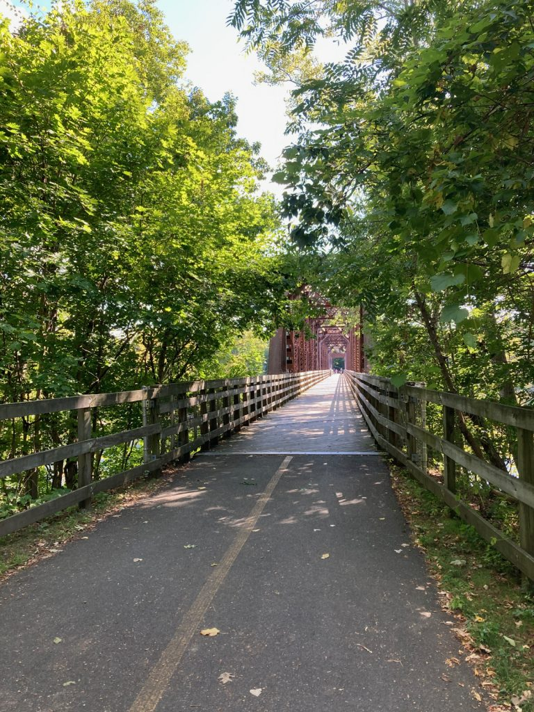 Looking along paved trail toward rusty-frame metal bridge (with wooden deck), and trees on either side of the trail.