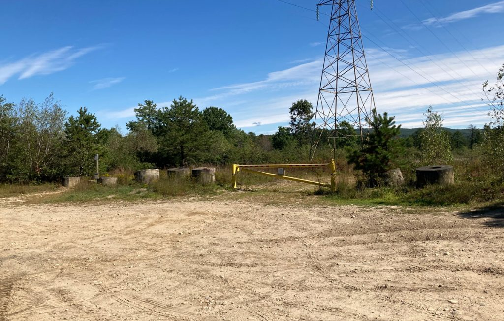 Dirt parking area, with traffic gate blocking a path, some trees and brush beyond that, plus an electric wire tower.