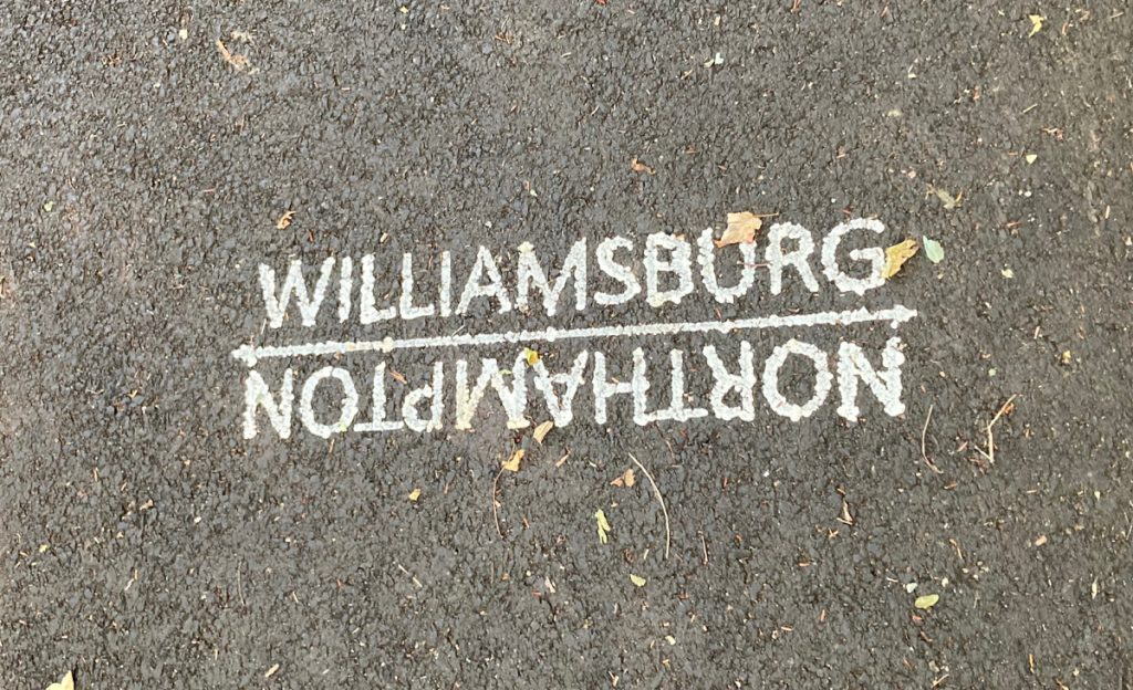 "White paint on pavement which reads ""Williamsburg"" on one side of a line, and then upside-down lettering on the other side of the line, reading ""Northampton""."