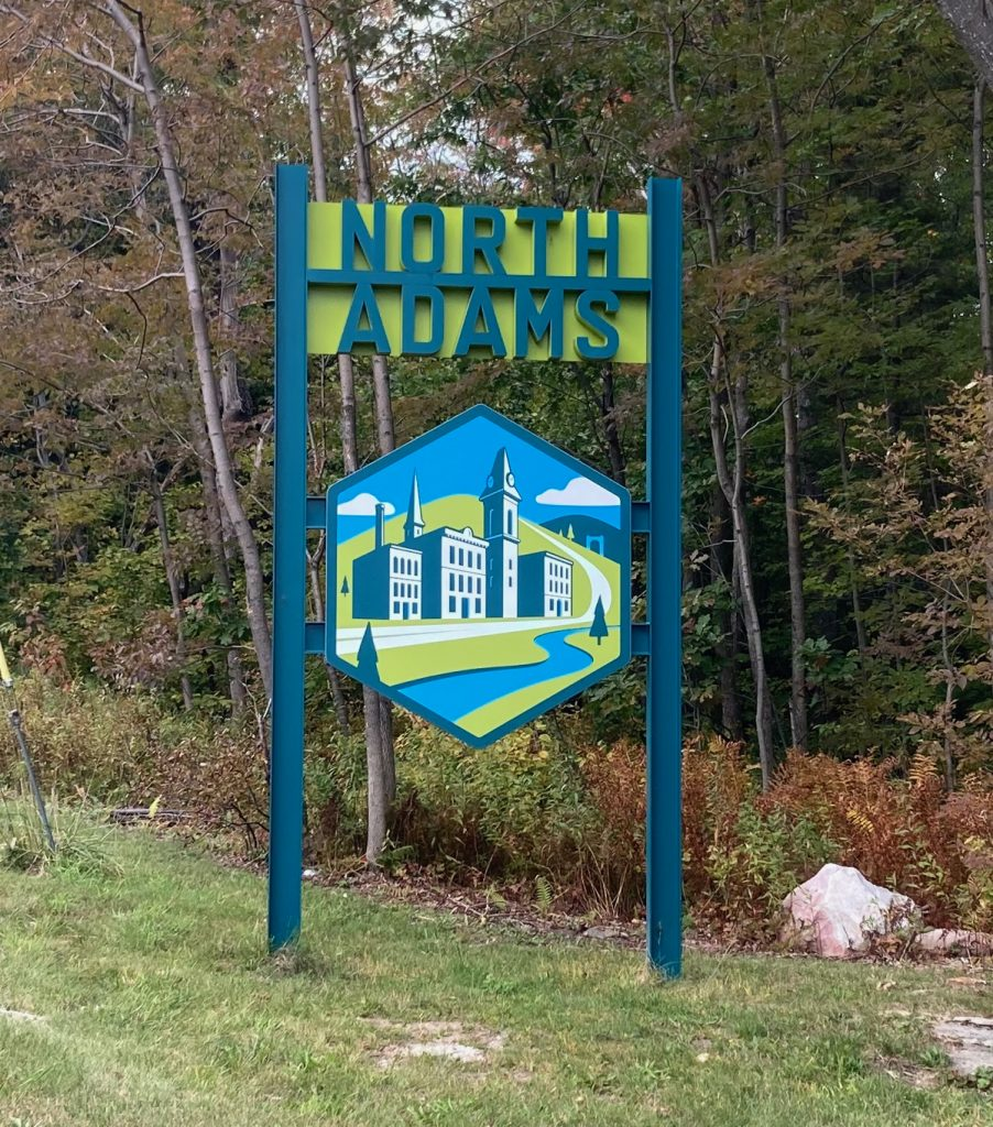 "Tall blue and green sign reading ""North Adams"", with a stylized image of old industrial buildings by a river and hills.  The sign stands in some grass by the edge of a wooded area."