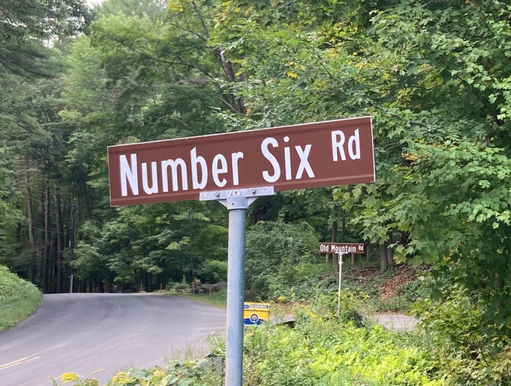 "Street sign reading ""Number Six Road"", with trees in background"