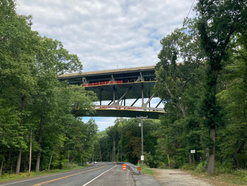 Road passing under a metal frame bridge, which is well above the road surface, with trees on either side of the road