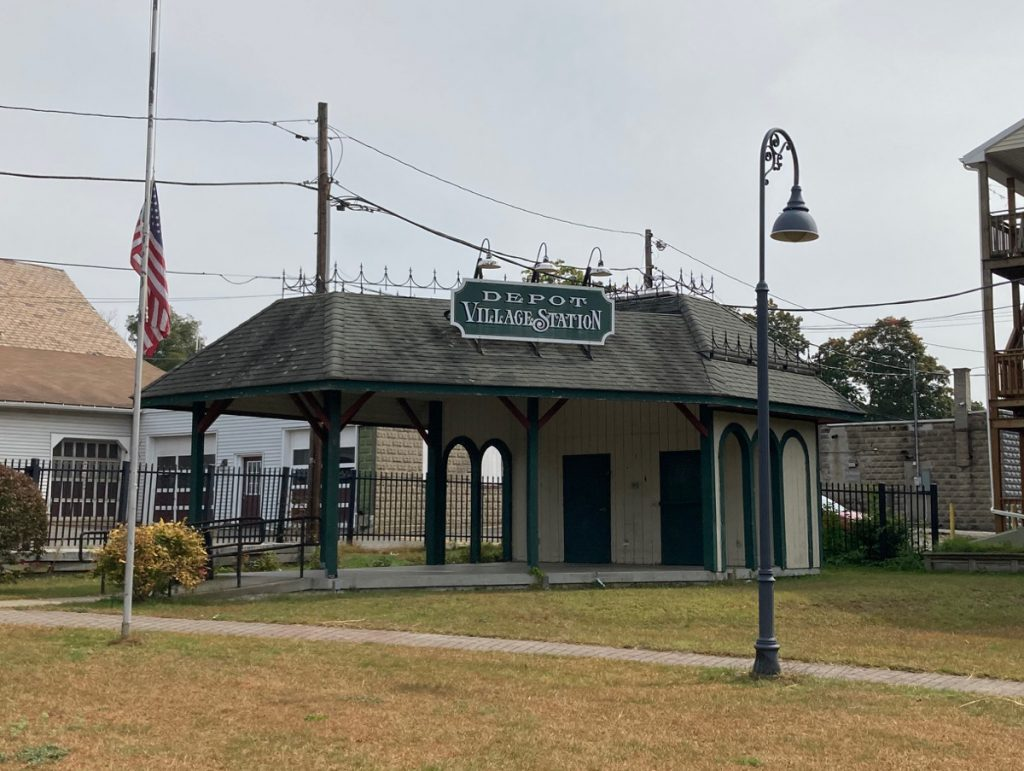 "Small building with open area under much of roof, with sign on it reading ""Depot Village Station"".  Grassy area in front of the building."
