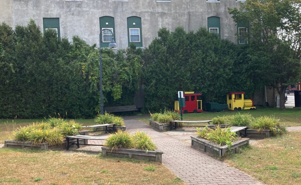 Small park with grass, brick walkway, benches, raised planters with perennials, and a small red and yellow play train.  Behind all of that are some small trees and a 2-story building.