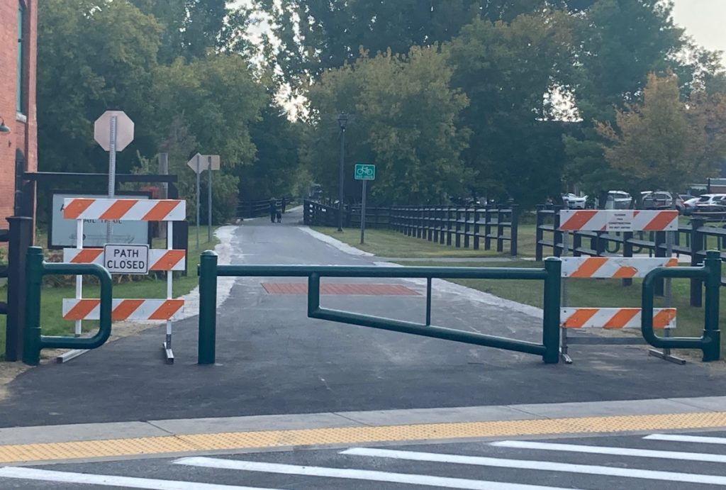 Looking along paved recreation trail with a green vehicle gate blocking much of the entrance, and orange and white construction signs blocking the small openings that bikes and pedestrians would normally use to enter the path section.  There are trees in the background, and some parked cars to the far right.