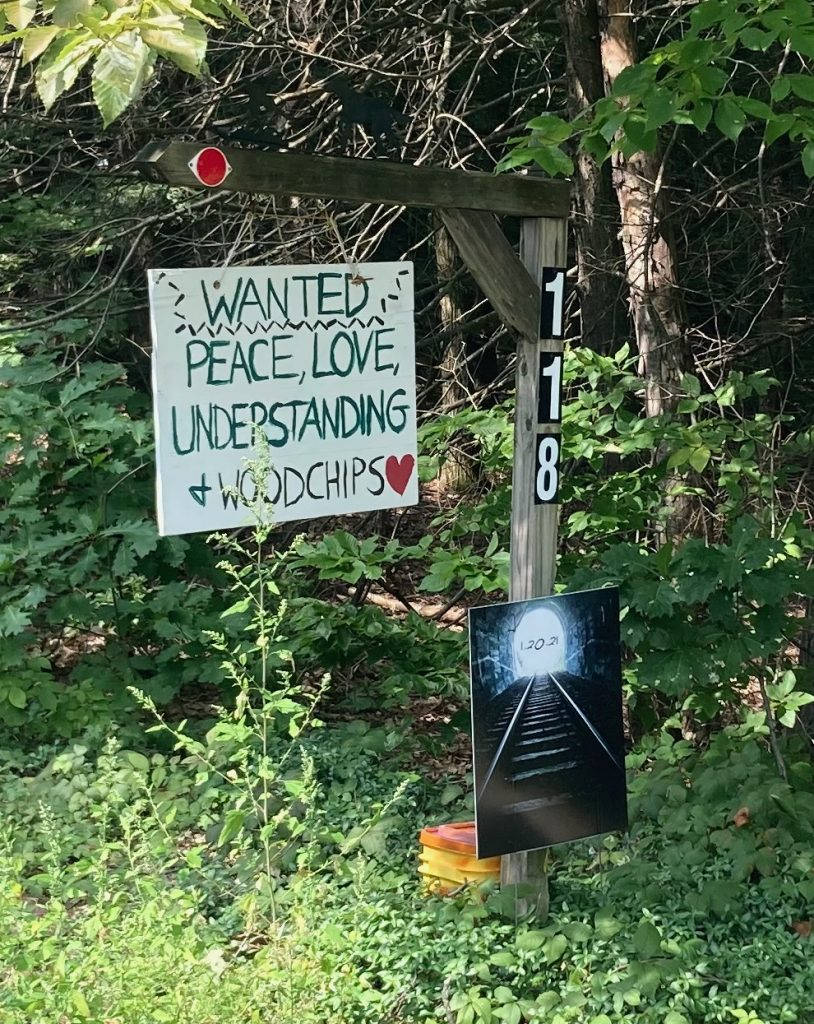 "Sign hanging from a wooden post that reads ""Wanted: peace, love, understanding, and wood chips"".  There is greenery all around."