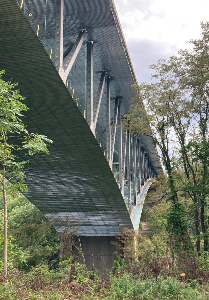 View from below of a bridge understructure, looking along the bridge to the far side