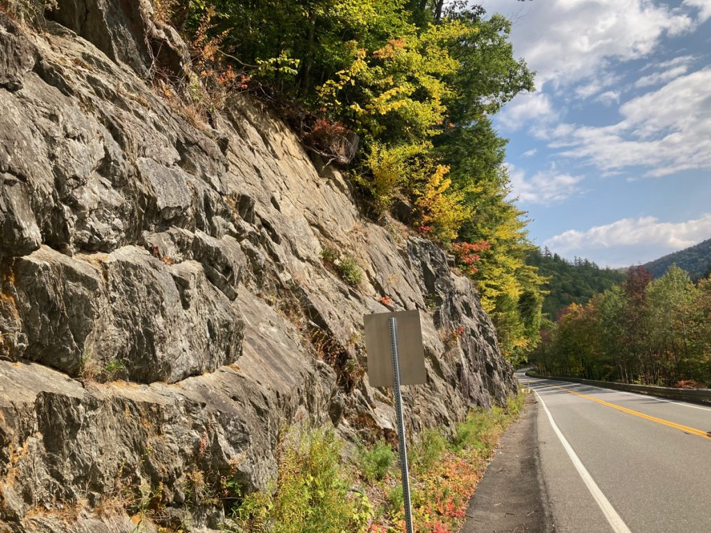 Rock face to the left of a road, with trees at the top of the rocks.  Some trees can be seen on the right side of the road.