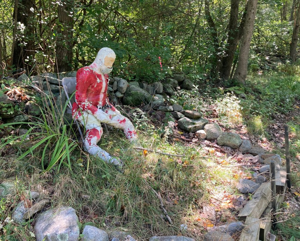 A very weathered, stuffed figure looking like Santa Claus, wearing a medical face mask, seated in grass and surrounded by a ring of stones.