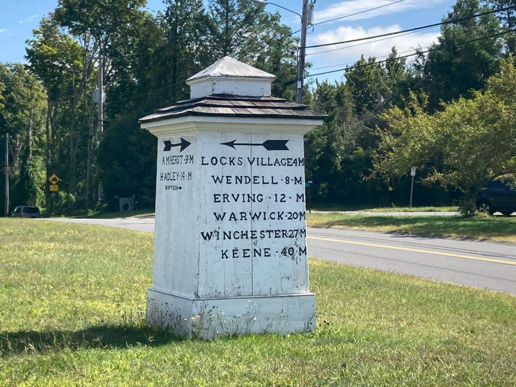 White, wooden 4-sided sign column, giving distances to different towns and areas in black text.  It stands in a field of grass and a road passes nearby, with trees in distance.
