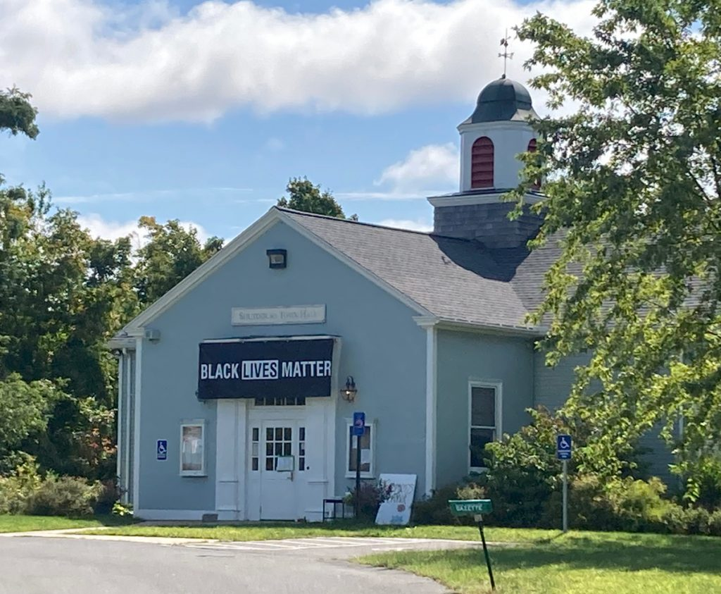"Shutesbury town hall building, painted a light-blue color, there is a large banner on the building reading ""Black Lives Matter"""