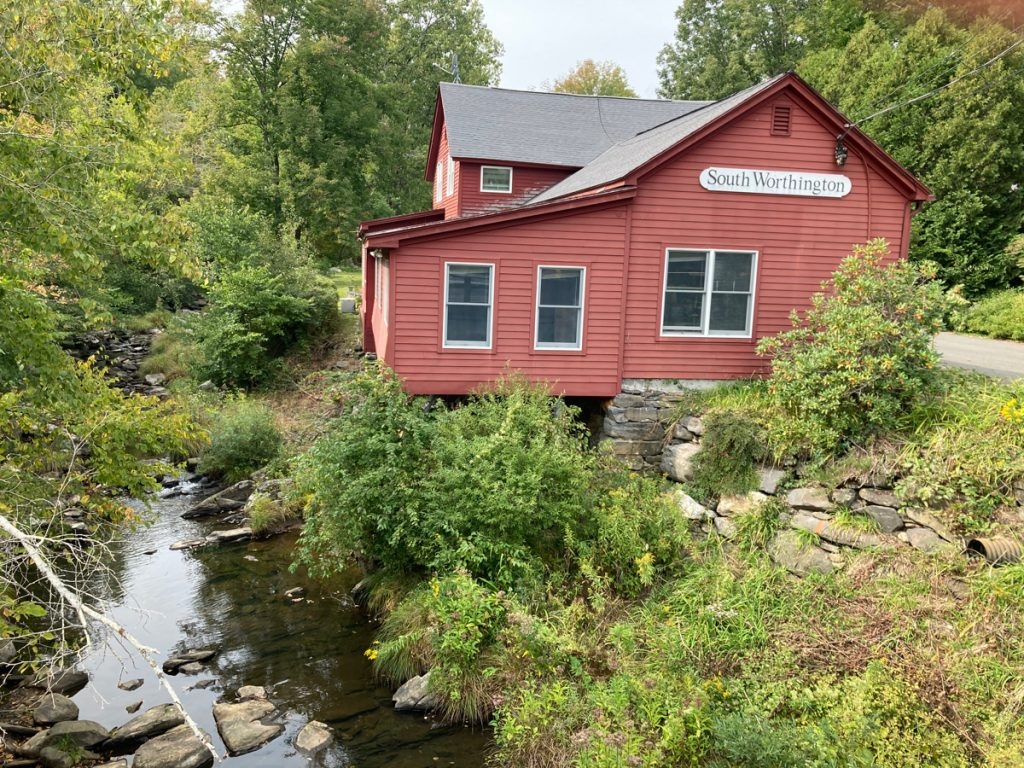 "Red building on the upper right of photo, with a sign on it reading ""South Worthington"".  A small river flows past in the lower left, and otherwise there are trees and brush around."