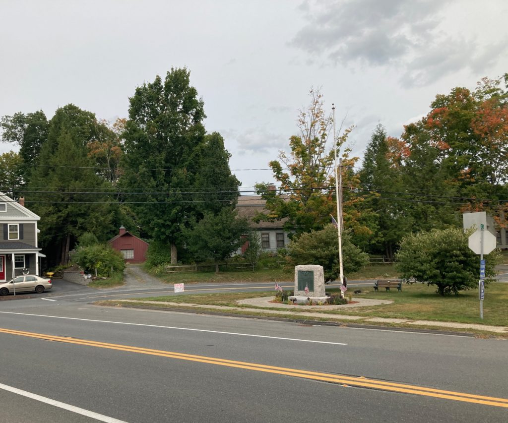 Road in the forground, with a stone marker and flagpole on grass on the other side of the road.  Trees and a couple of houses can be seen beyond a side street.