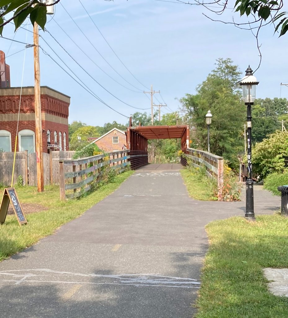 Looking along paved trail, just ahead there are wood fences on either side and the rusty-red frame of a bridge in the distance