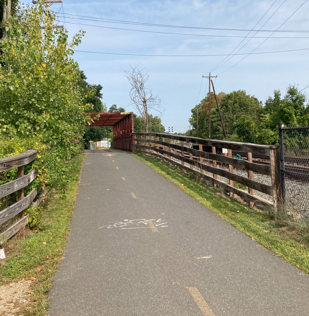 Looking along paved trail, there are wood fences on either side and the rusty-red frame of a bridge in the distance.  Railroad tracks can be seen to the right.