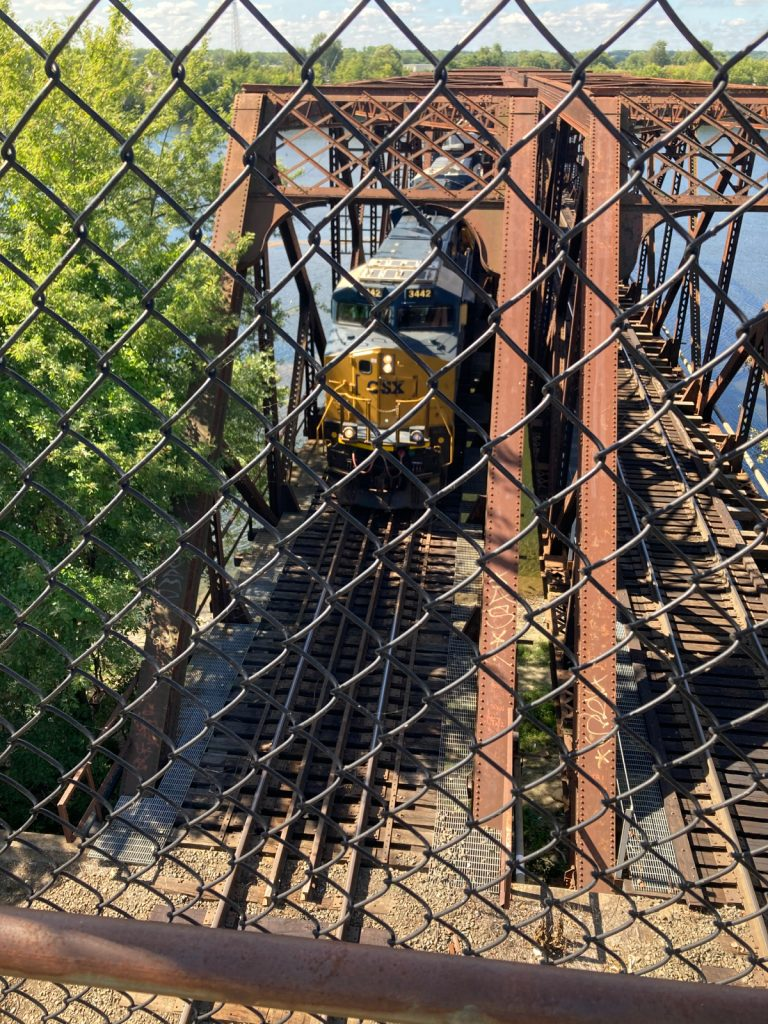 Looking down through chainlink fence at a train coming off of a bridge, toward the camera