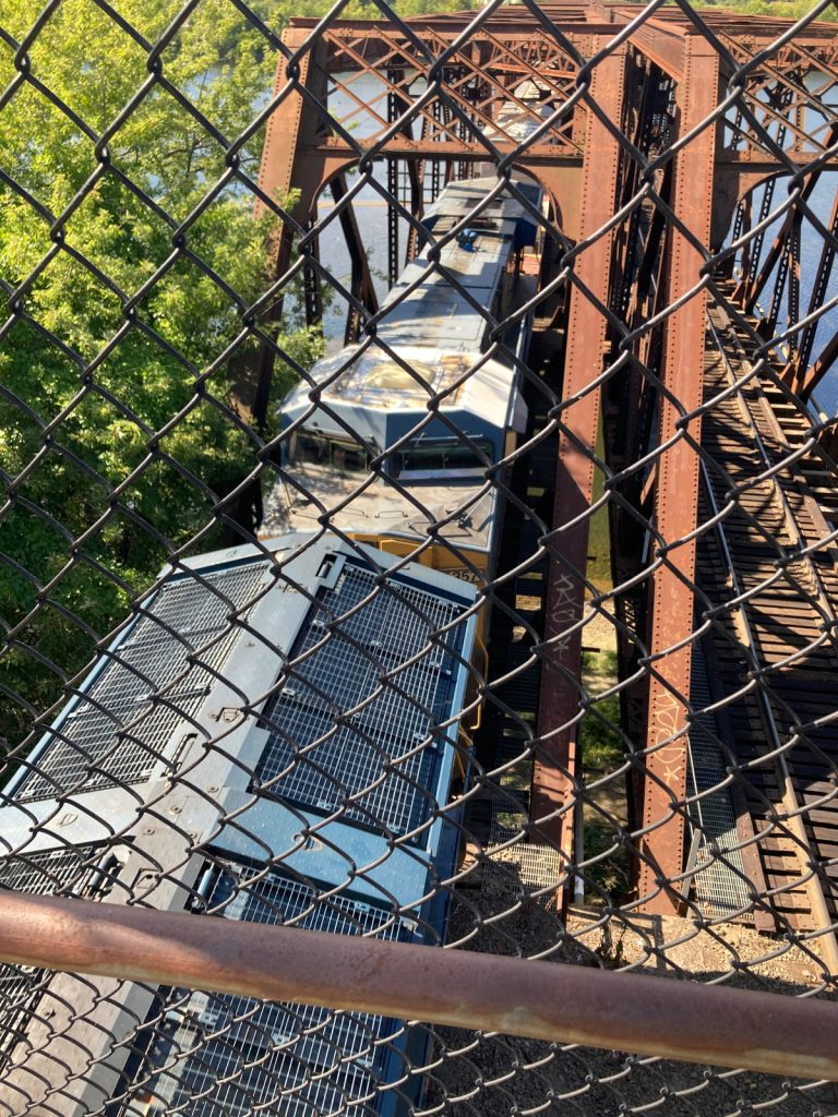Looking down through chainlink fence at a train coming off of a bridge, passing under the camera