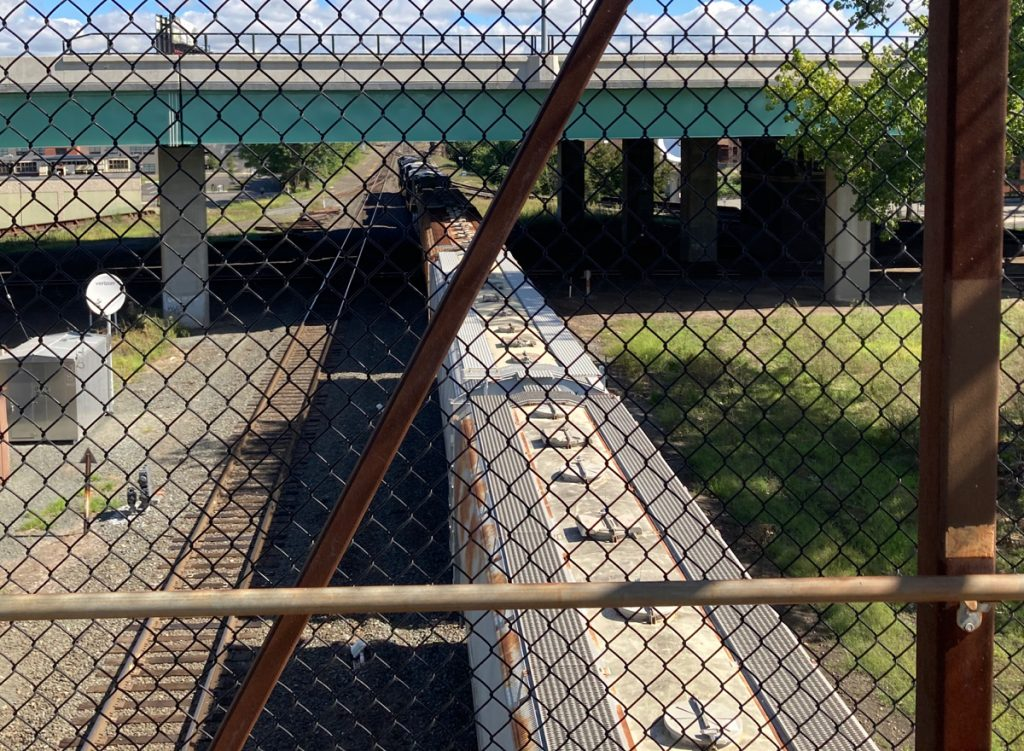Looking down through chainlink fence at a train heading away from the camera