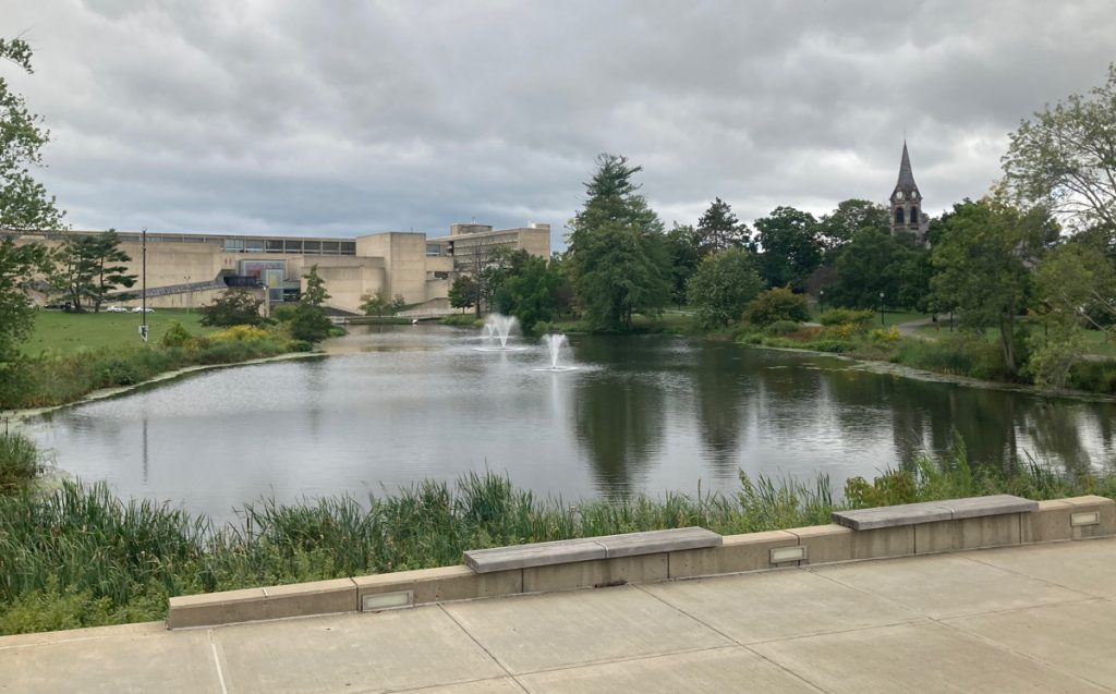 Large pond on the campus of the university of massachusetts.  Buildings and trees can be seen around it.