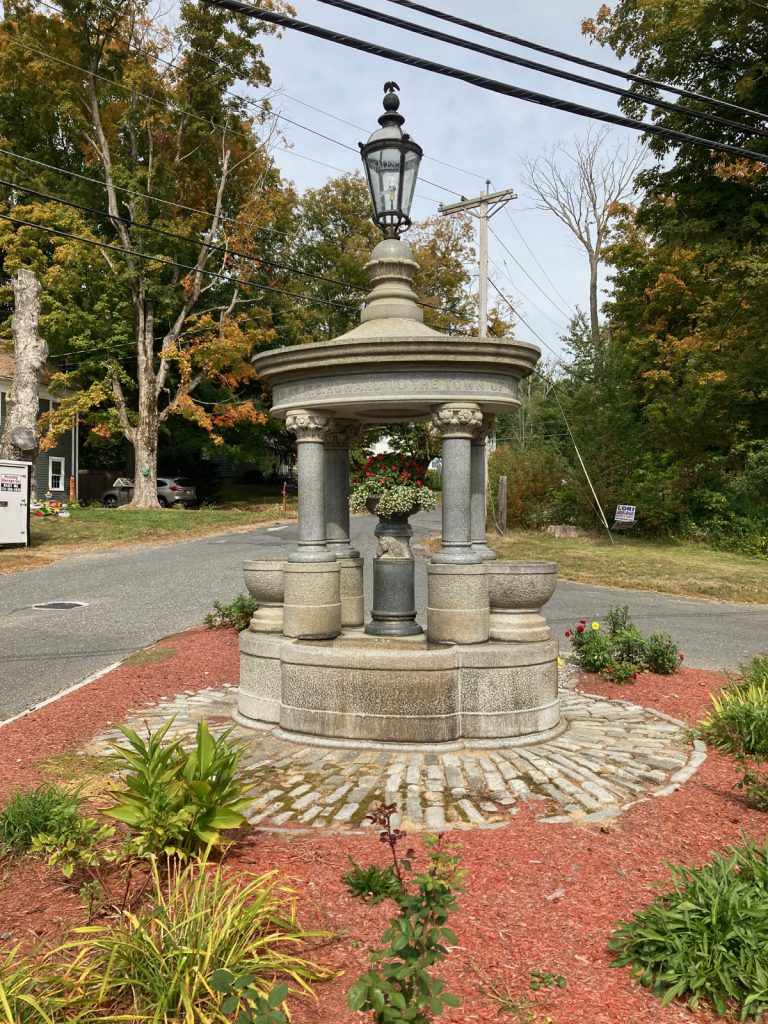 Stone monument which includes four pillars on a round base, with a planter containing flowers between the columns, a platform on top of the columns, and that is topped off by a glass and iron lamp.  There is some landscaping with red wood chips around the monument, with a road and trees in the background.