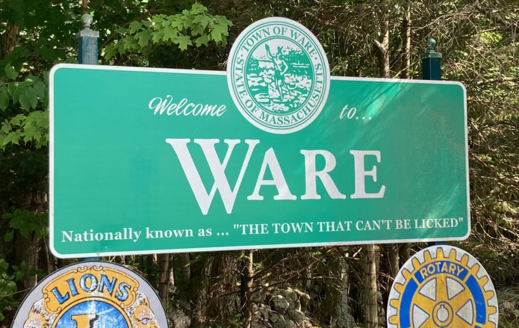 "Large green roadside sign reading ""Welcome to Ware.  Nationally known as the town that can't be licked."""