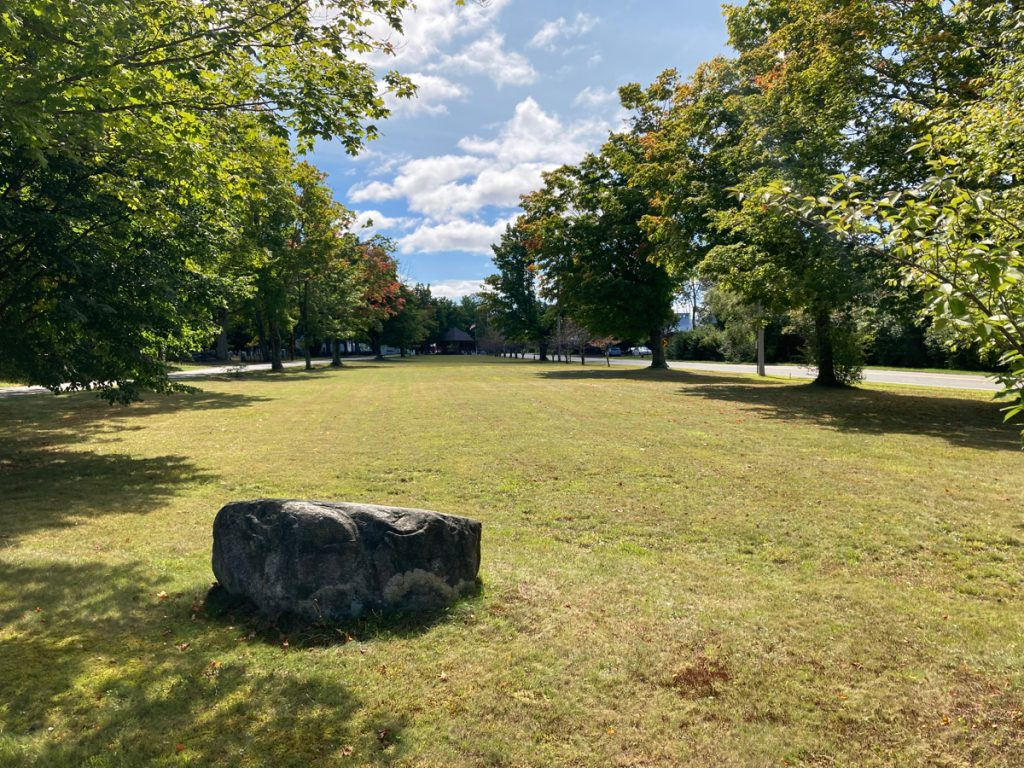 Long field of grass on town common.  There is a large rock in the foreground, and trees line each side of the common.
