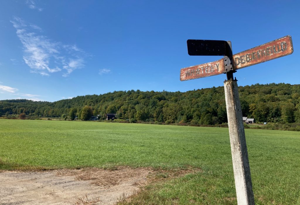"Grassy plain with trees and hills in background, and a signpost in the foreground reading ""Town Line"", ""Whately"", and ""Deerfield""."
