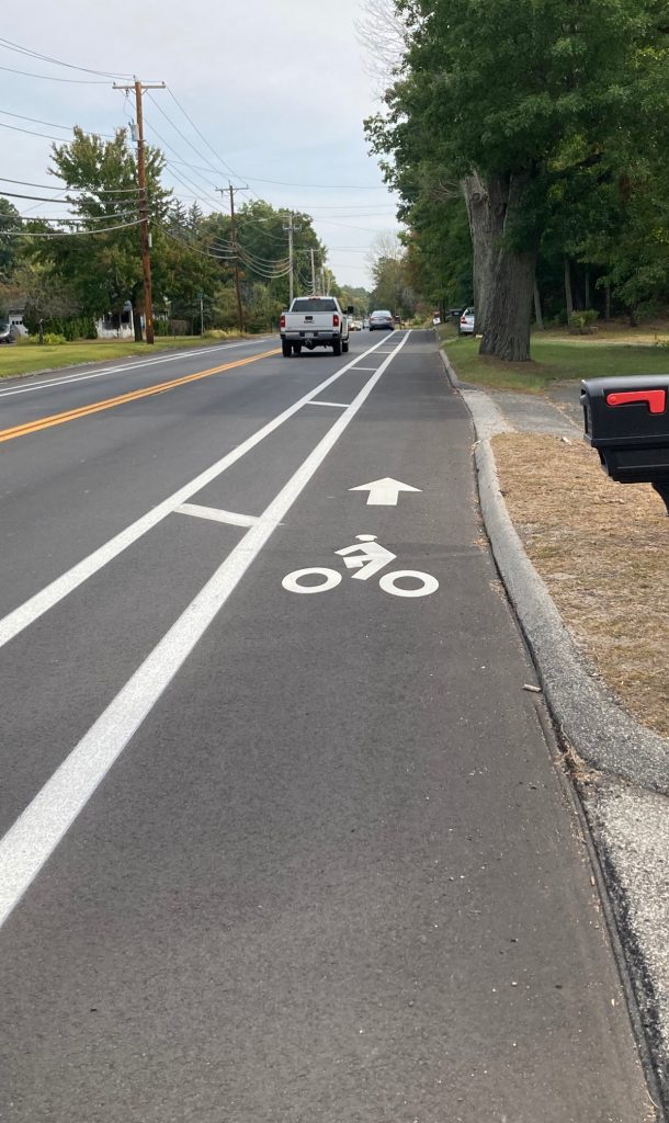Road surface with bike lane painted on it, stretching off into distance, with some trees on the side of the road a ways away.