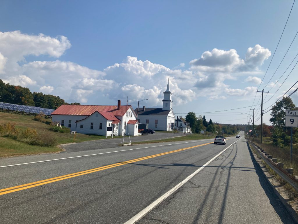 Looking along road, there are some buildings on the left side, including a church, and a white building with a shiny copper roof.
