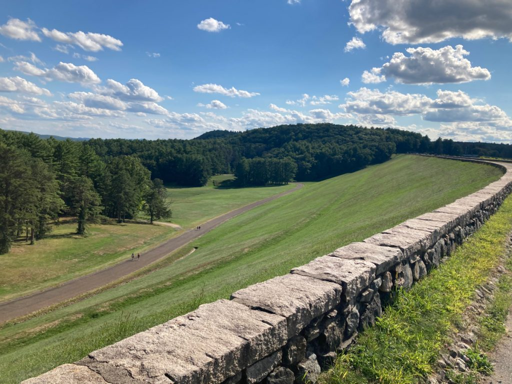 Grassy slop of a large earthen dam, with a short stone wall running along the top of it.  Some people can be seen at a distance, walking on a path at the bottom of the slope.