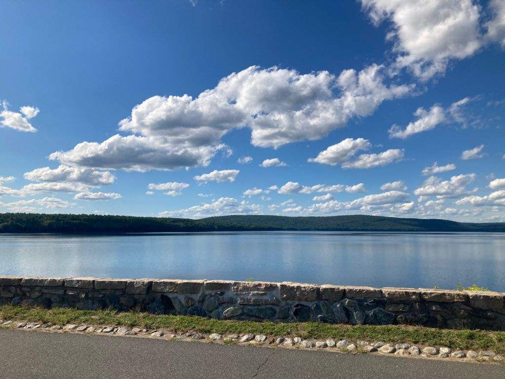 Water of Quabbin reservoir, with top surface of dam in foreground, and hills in background, clouds in sky