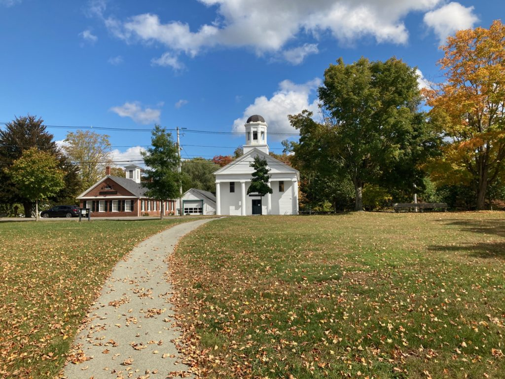 Grassy town common with paved sidewalk going through the middle.  At the far side of the grass the sidewalk leads to a white building with a cupola on top.  There is a shorter brick building next to the white one, and trees among and behind the buildings.  There are numerous dry, fallen leaves on the grass.